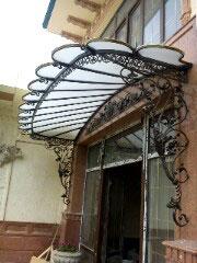 Кованые навесы: из поликарбоната и других материалов, над дверью, на балкон, дву- и односкатные, художественные, с металлическими столбами, отличия от козырьков